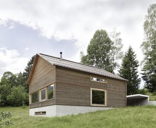 """13 Epic Alpine Retreats We're Swooning Over - Photo 12 of 13 - Guided by the region's traditional alpine farmhouses, Austrian firm Innauer Matt Architekten designed the house as a simple wooden building resting atop a solid, reinforced concrete plinth. The striking pitched roof is made of copper with its gable looking down towards the valley, and horizontal larch cladding was used for the façade to give the house an interesting ribbed texture with deep grooves. <span style=""""color: rgb(204, 204, 204); font-size: 13px;"""">Courtesy of Adolf Bereuter</span>"""
