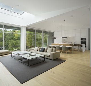 A Lakeside Retreat in Quebec Looks Sharp With a Blade-Like Roof - Photo 5 of 13 - A skylight brings plenty of natural light into the living room.