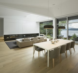 A Lakeside Retreat in Quebec Looks Sharp With a Blade-Like Roof - Photo 10 of 13 - The living and dining areas have ceilings that reach as high as 25 feet in sections.