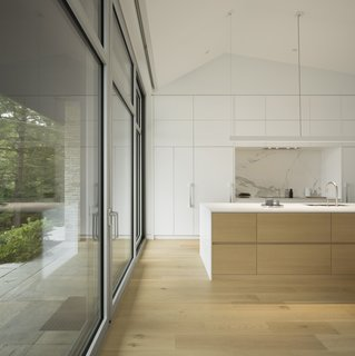 A Lakeside Retreat in Quebec Looks Sharp With a Blade-Like Roof - Photo 9 of 13 - The white kitchen appears as if it were an extension of the walls and ceilings.