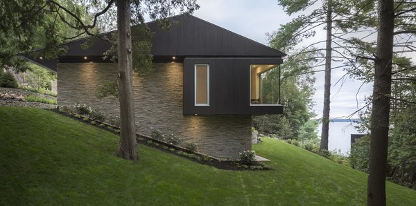The house dips down the slope, creating the impression of house that's half sunk into the ground.