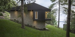 A Lakeside Retreat in Quebec Looks Sharp With a Blade-Like Roof - Photo 2 of 13 - The house dips down the slope, creating the impression of being half buried in the ground.