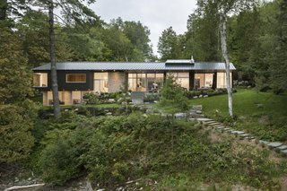 A Lakeside Retreat in Quebec Looks Sharp With a Blade-Like Roof - Photo 3 of 13 - The lake-facing side of the house is fitted with floor-to-ceiling glass windows.