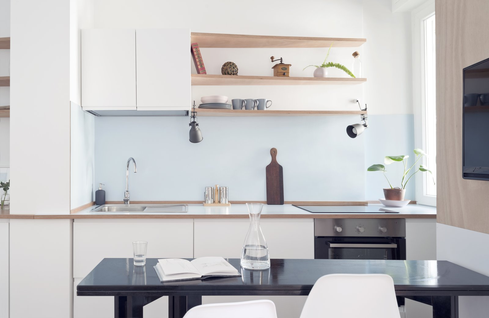 A small kitchenette and dining room is located the the windows.