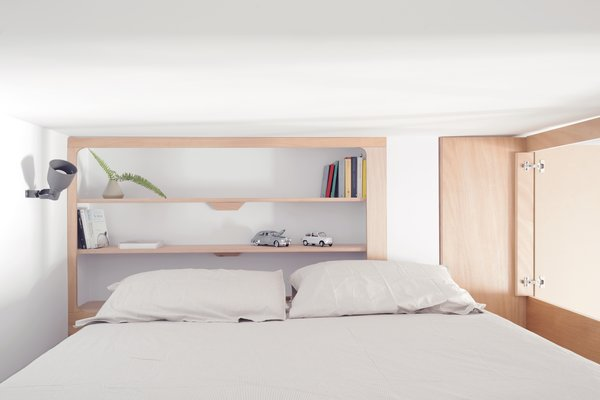 The cabin-like bedroom contains a king-sized bed and minimalist built-in shelves.
