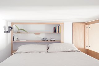 A Tiny Apartment in the Italian Riviera Takes Cues From Nautical Design - Photo 5 of 9 - The cabin-like bedroom contains a king-size bed and minimalist, built-in shelves.