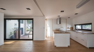 A Gabled Corridor Runs Through This Playful South Korean Home - Photo 6 of 13 - The kitchen and door that opens to a courtyard
