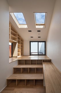 A Gabled Corridor Runs Through This Playful South Korean Home - Photo 7 of 13 - Steps with storage that lead up to the balcony