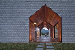 A Gabled Corridor Runs Through This Playful South Korean Home - Photo 2 of 13 - Fitted on all sides with warm wood, this double-height, gable-shaped passageway serves as the entrance to the house.