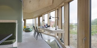 A Tent-Shaped Home in the Netherlands Crouches Between Natural Dunes - Photo 5 of 11 - A study desk built into the glass walls on the ground floor provides a workspace with views.