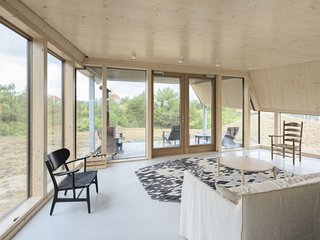 A Tent-Shaped Home in the Netherlands Crouches Between Natural Dunes - Photo 8 of 11 - The porch is easily accessible from the living lounge.