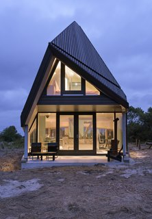 A Tent-Shaped Home in the Netherlands Crouches Between Natural Dunes - Photo 4 of 11 - A covered porch on the ground floor