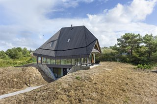 A Tent-Shaped Home in the Netherlands Crouches Between Natural Dunes - Photo 6 of 11 - Under the roof are a basement, ground level, and attic. The basement level holds the bedrooms and uses the natural dunes as a privacy screen.