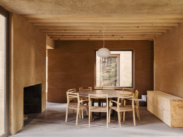 A minimalist dining table and large fireplace.