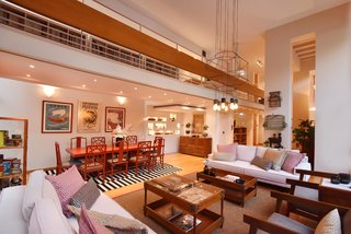Live Large in These 10 Loft-Style Vacation Rentals - Photo 4 of 10 - This loft-style apartment comes equipped with a mezzanine that runs the length of the space.