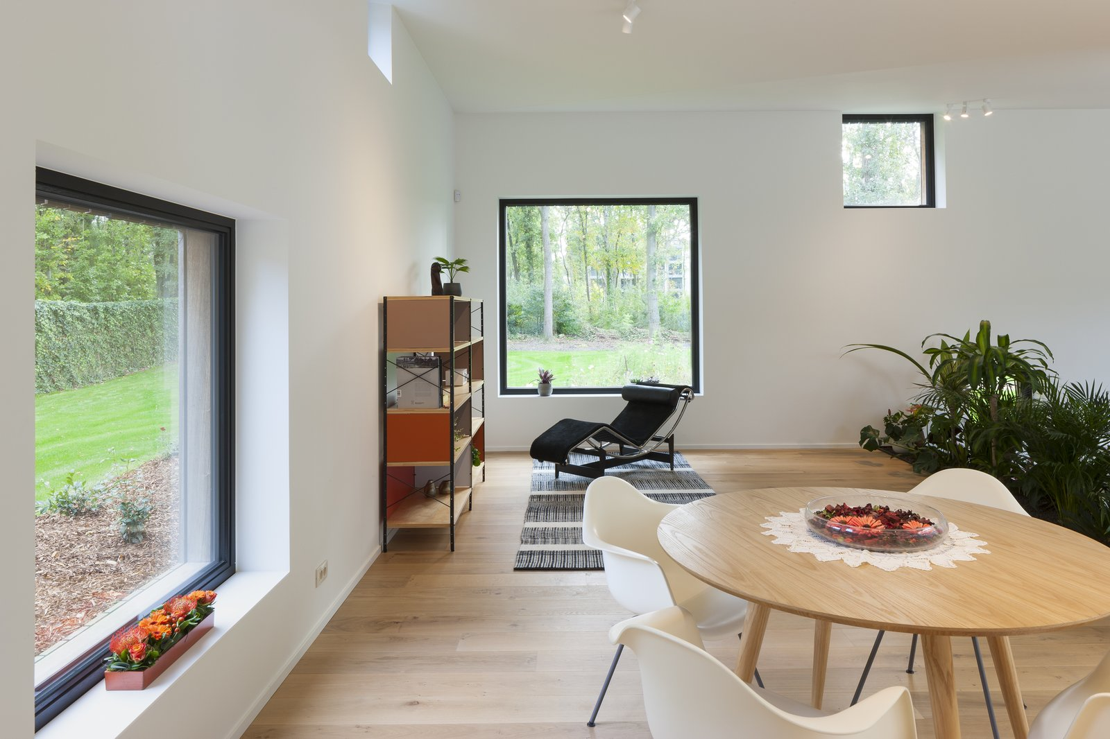 A black Arne Jacobsen Series 07 chair from Fritz Hansen, Eames storage shelf from Vitra and white Eames DAX plastic armchairs.
