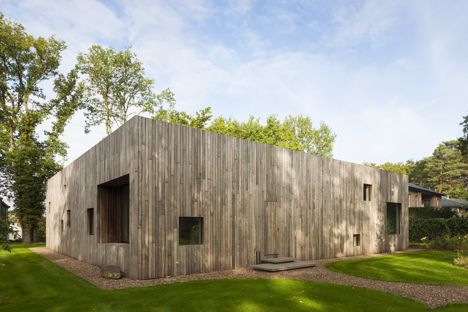Several square perforations of varied sizes along wooden facade serve as windows.