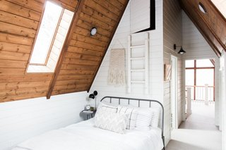 Before and After: An A-Frame Cabin Boasts Serious Scandinavian Vibes - Photo 7 of 14 - Plaid pillows and a weave on the wall bring a folksy feel to the bedroom.