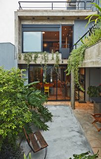 This Slender Concrete Home in Brazil Feels Like an Urban Jungle - Photo 2 of 13 - The backyard garden has an outdoor grilling station.