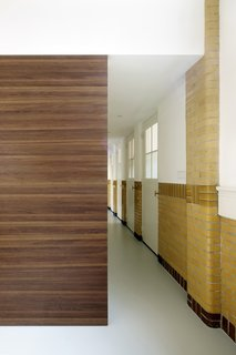 A 20th-Century Dutch Schoolhouse Now Holds a Series of Airy Lofts - Photo 8 of 13 - A wooden box, which houses a walk-in closet and stairs to the bedrooms, acts as a partition that dissects the hallway.