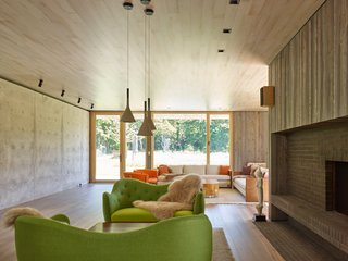 This Stunning Suffolk County Home Brings a Modern Twist to a Historic Area - Photo 8 of 18 - Above is a green Finnjuhl sofa and table at the fireplace, as well as pendants from Foscarini.