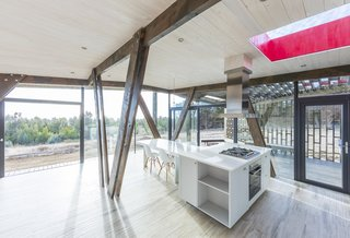 """This """"Almost Cube"""" House Offers Mesmerizing Views of the Chilean Coast - Photo 5 of 12 - The light wood floors and glossy white kitchen give the interior a bright and minimalist feel."""