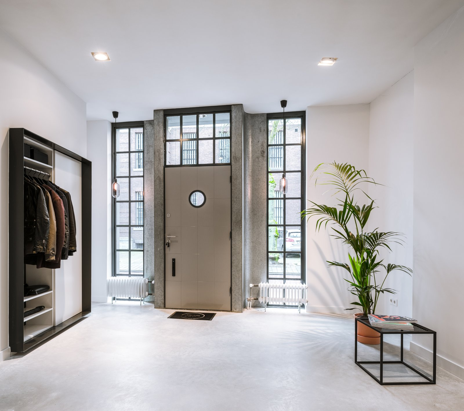 Glass windows help connect the entrance foyer to the street outdoors. Tagged: Doors, Metal, Swing, and Exterior.  Best Doors Photos from A 19th-Century Dutch Workshop Is Now a Stunning, Spacious Loft
