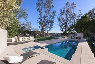 Red Hot Chili Peppers Frontman Anthony Kiedis' Former L.A. Abode Asks $3.2M - Photo 11 of 13 - An outdoor kitchen, green lawn, and pool make the rear yard a perfect spot for outdoor soirees.