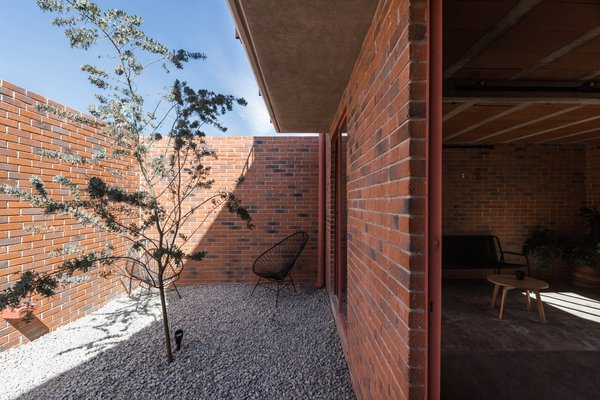 A courtyard helps isolate the interior of the house visually and acoustically from its urban surroundings, and provides a large opening on the envelope of the house, where light and shadow play enhance the colors and textures of the building throughout the day.