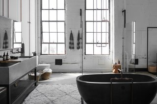 A 1920s Office Space Is Transformed Into a Polished Penthouse - Photo 9 of 13 - An oversized, custom-made concrete trough on a bronze base is paired with industrial copper piping and taps.  The mirror, which is suspended from the ceiling by braided leather straps,  was manufactured by PSS Design Cult. The oval bathtub is from NativeStone.