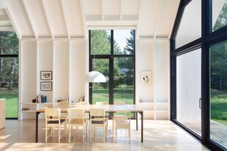 A Dreamy Lakeside Cottage Embodies the Spirit of Simple Living - Photo 6 of 11 - Three tall glass panels are fitted along both sides of the house, making the inside space feel similar to a light-filled pavilion.
