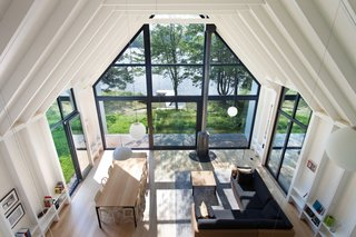 A Dreamy Lakeside Cottage Embodies the Spirit of Simple Living - Photo 4 of 11 - Floor-to-ceiling glass windows seamlessly connect the indoor spaces to the outdoors.