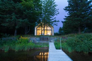 A Dreamy Lakeside Cottage Embodies the Spirit of Simple Living - Photo 7 of 11 - A small porch on the southern facade leads down to the lake.