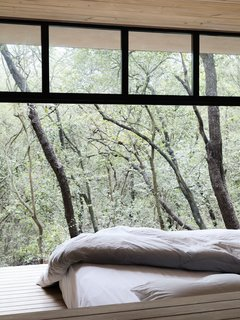 A Mirrored Mexican Home Hides Among a Lush Forest - Photo 12 of 15 - A peek at one of the bedrooms that looks out to the tree tops.