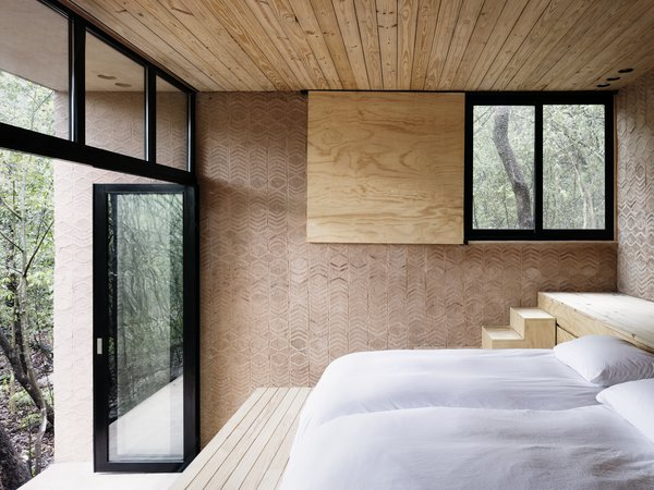 Rammed earth, brick and wood give the bedroom a warm, rustic atmosphere.