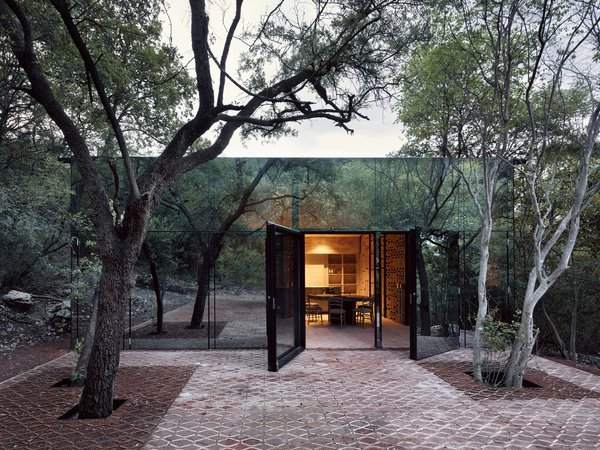 Mirrored glass allows this holiday home in Mexico to blend in with it's woodland site.