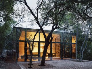 A Mirrored Mexican Home Hides Among a Lush Forest - Photo 2 of 15 - The living lounge, dining area, and kitchen are located within the larger of the two volumes.