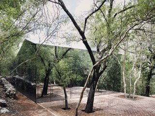 A Mirrored Mexican Home Hides Among a Lush Forest - Photo 1 of 15 - The larger volume has a peaked roof and a mirrored facade, allowing the home to hide among the surrounding forest.