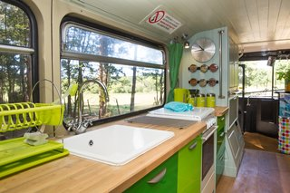 This Double-Decker Bus Offers an Eclectic Glamping Experience - Photo 5 of 12 - The kitchen comes with a sink, oven and cooktop.