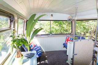 This Double-Decker Bus Offers an Eclectic Glamping Experience - Photo 8 of 12 - The original seats of the bus were restored to create a relaxing lounge area.