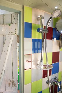 This Double-Decker Bus Offers an Eclectic Glamping Experience - Photo 4 of 12 - A shower is located in the wet room.