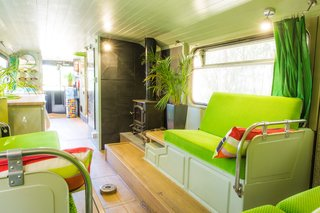 This Double-Decker Bus Offers an Eclectic Glamping Experience - Photo 2 of 12 - A log-burning fireplace is available for use, which comes in handy during the winter months.