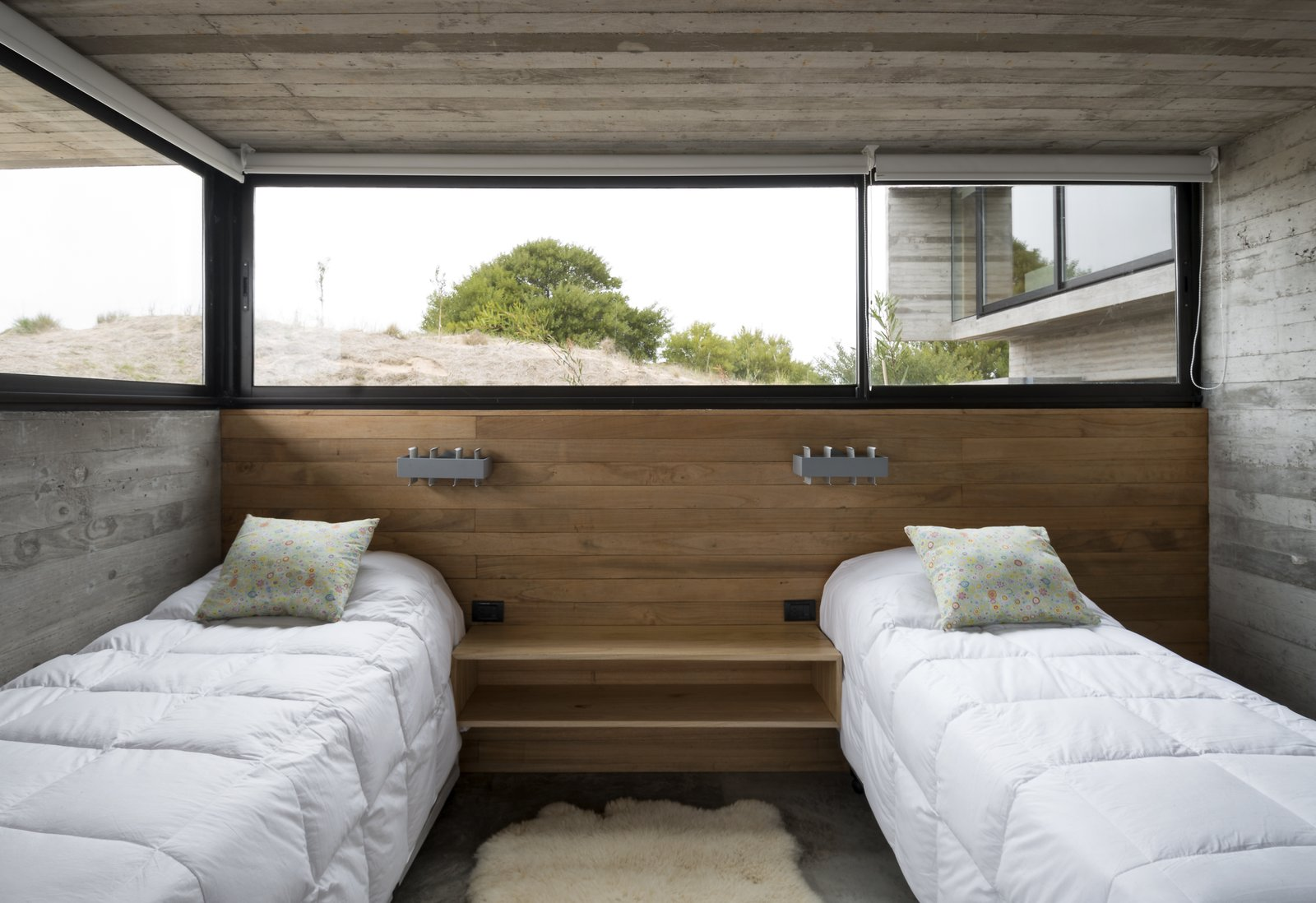 A guest bedroom that's partially submerged in the dunes. Tagged: Bedroom, Bed, Wall Lighting, Concrete Floor, Night Stands, and Shelves.  Best Photos from This Stacked Concrete Home Is Not Your Typical Golf Course Dwelling