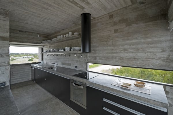 A streamlined kitchen with a concrete slab countertop.