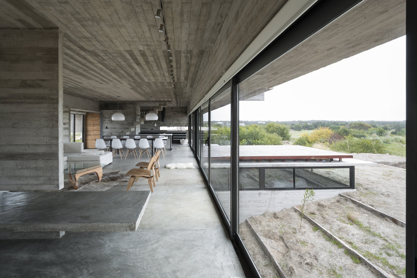 Layered concrete walls and ceilings add a raw masculinity to the interiors. Tagged: Living Room, Sofa, Concrete Floor, Coffee Tables, Chair, and Track Lighting.  Best Photos from This Stacked Concrete Home Is Not Your Typical Golf Course Dwelling