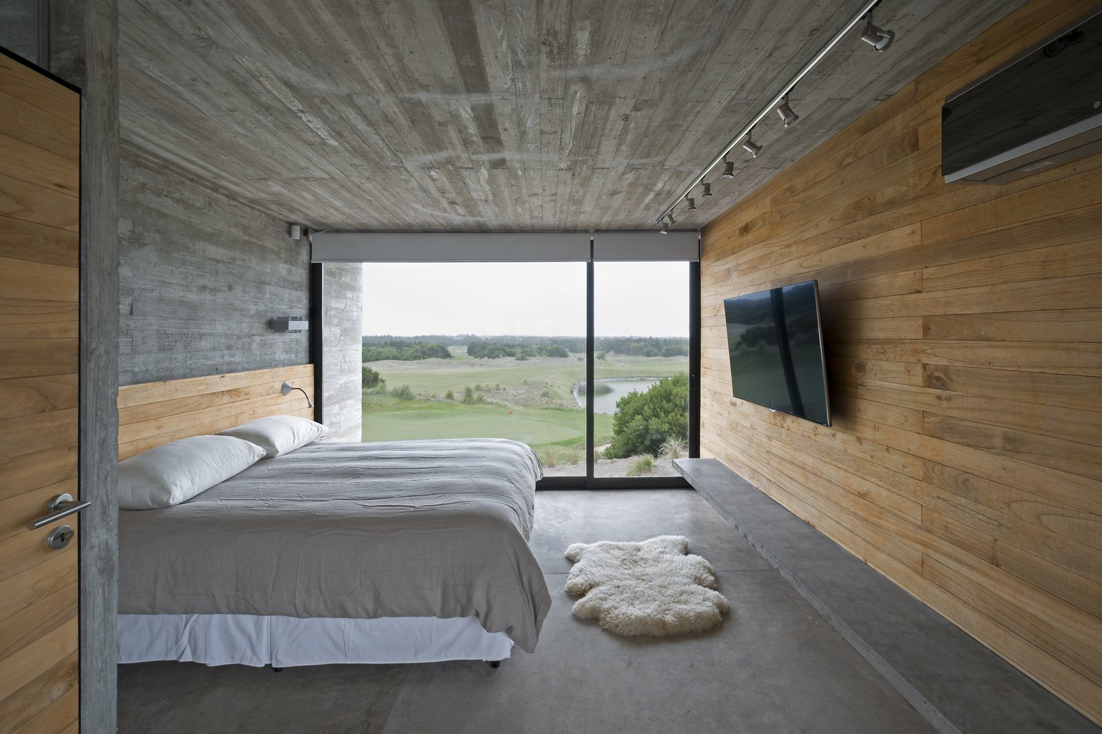 Kiri wood walls help keep the bedroom cool. Tagged: Bedroom, Track Lighting, Bed, and Concrete Floor.  Best Photos from This Stacked Concrete Home Is Not Your Typical Golf Course Dwelling