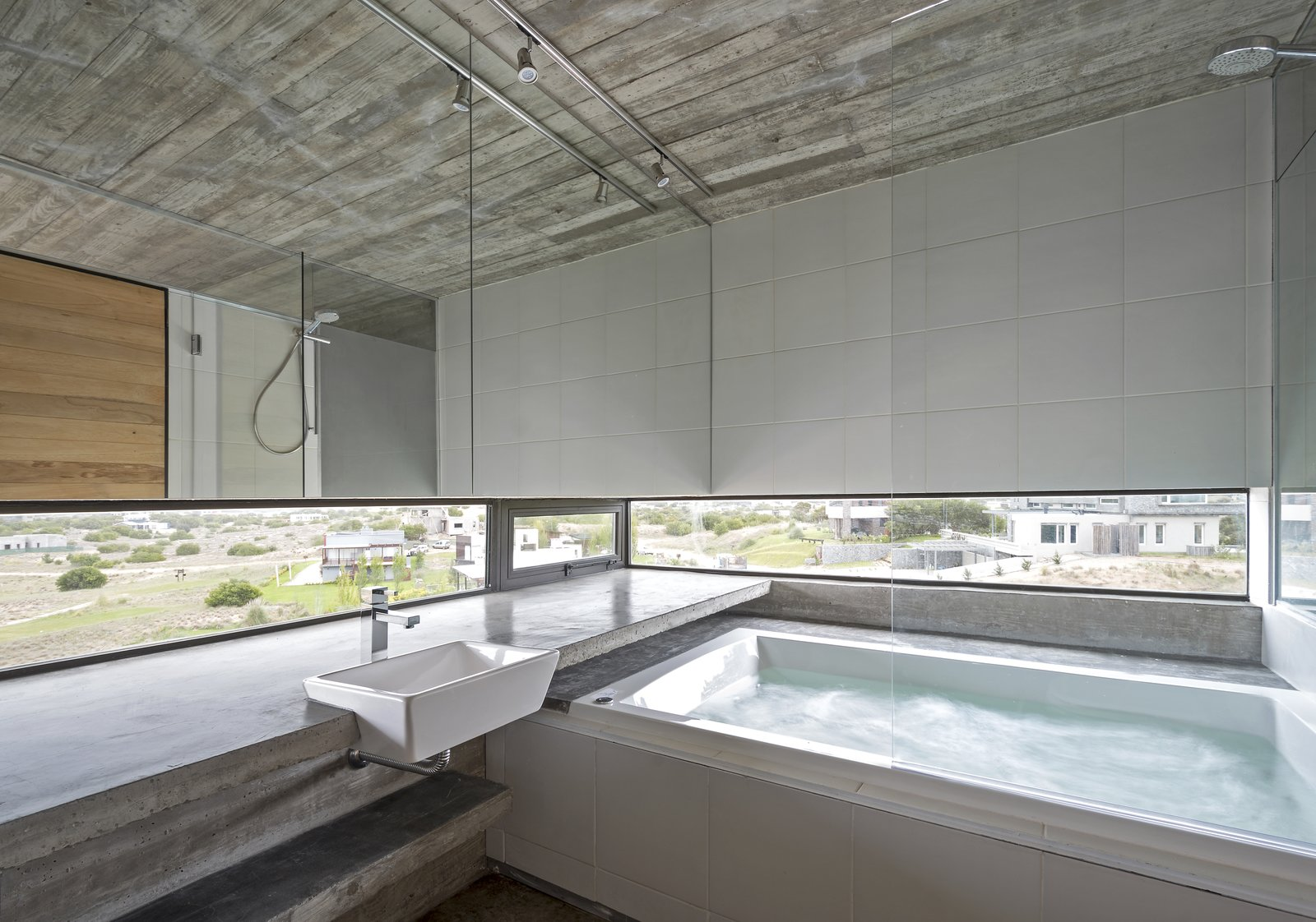 A jacuzzi bathtub that looks out fo views of the neighborhood. Tagged: Bath Room, Concrete Counter, Whirlpool Tub, Concrete Floor, Undermount Sink, and Track Lighting.  Best Photos from This Stacked Concrete Home Is Not Your Typical Golf Course Dwelling
