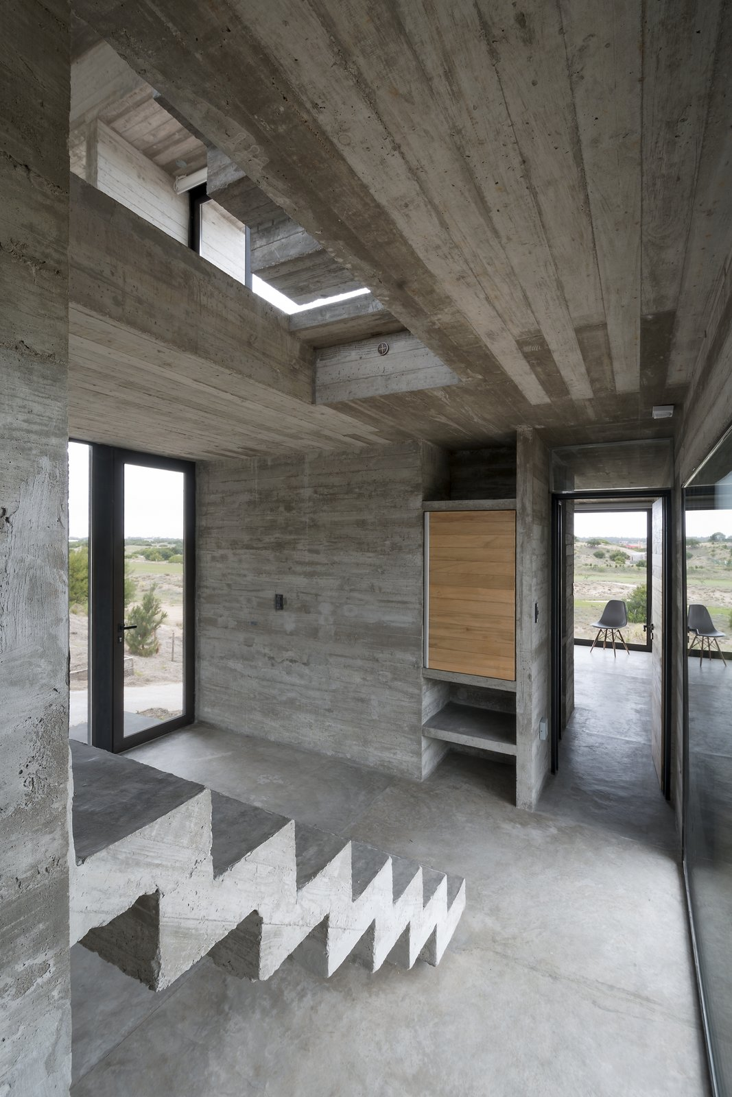 Exposed concrete is used for the rail-less stairs. Tagged: Staircase and Concrete Tread.  Best Photos from This Stacked Concrete Home Is Not Your Typical Golf Course Dwelling