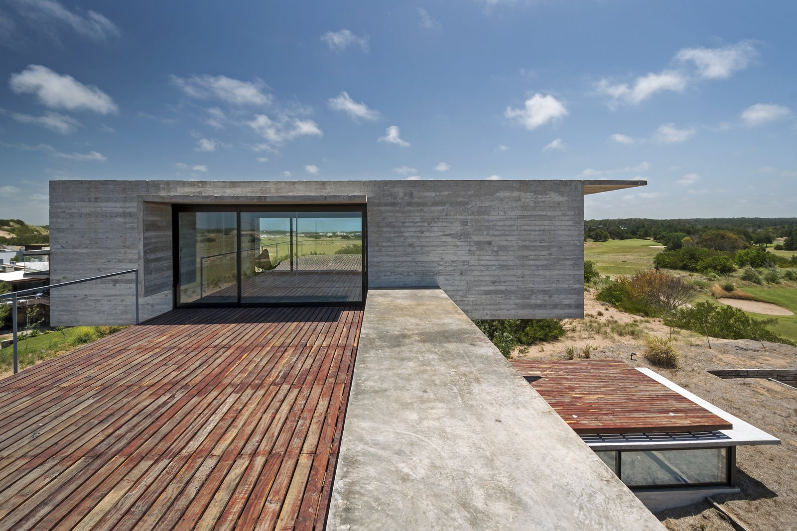 The large outdoor terraces make the outdoors a major part of the house's design. Tagged: Outdoor, Side Yard, Wood Patio, Porch, Deck, Large Patio, Porch, Deck, and Metal Fences, Wall.  Best Photos from This Stacked Concrete Home Is Not Your Typical Golf Course Dwelling