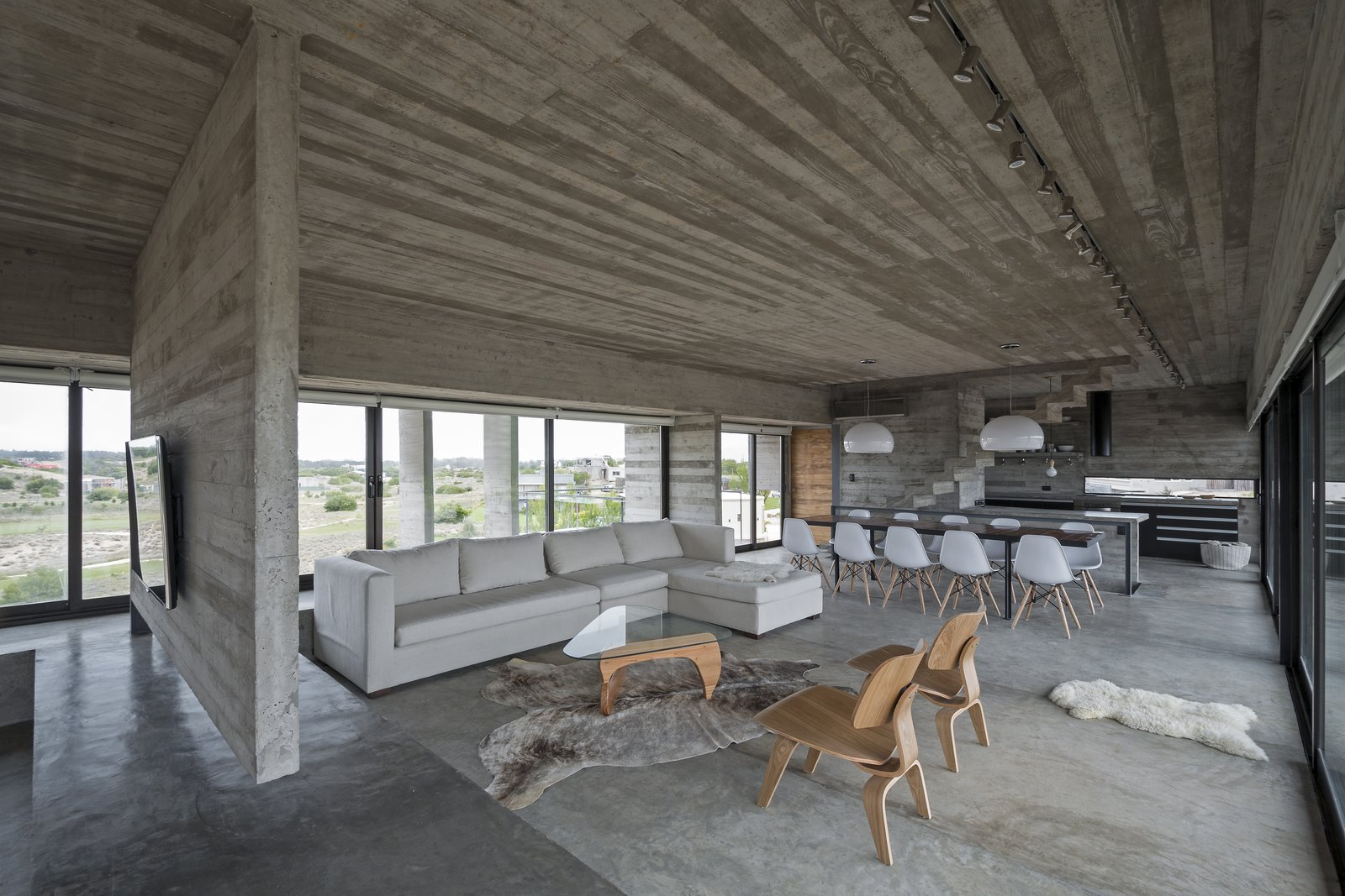Elegant, cream and white colored sofa and chairs, and wood details compliment the raw concrete fitouts beautifully. Tagged: Living Room, Sectional, Concrete Floor, Chair, Coffee Tables, and Pendant Lighting.  Best Photos from This Stacked Concrete Home Is Not Your Typical Golf Course Dwelling